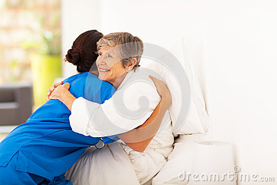 Elderly hugging caregiver