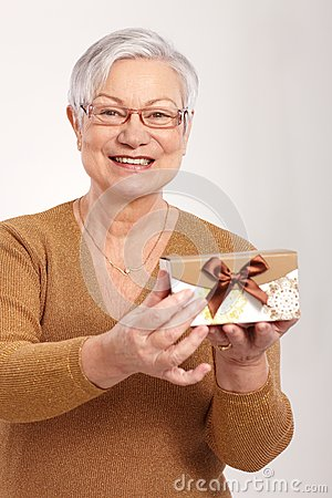 Elderly lady holding small present box smiling