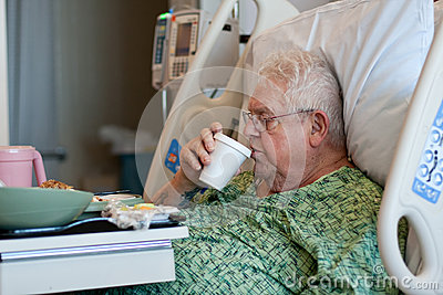 Elderly male hospital patient drinks water