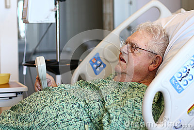 Elderly male hospital patient holds TV remote