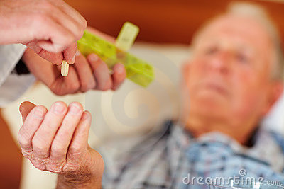 Elderly man being given a pill by a doctor