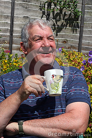 Elderly man close up drinking coffee outside.