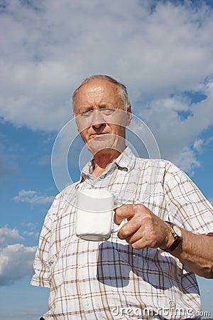 An elderly man drinks tea on nature