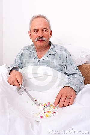 Elderly man eating meds