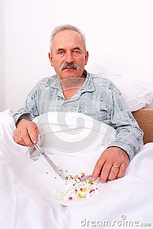 Elderly man eating meds