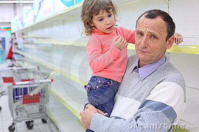 Elderly man at empty shelves in shop with child