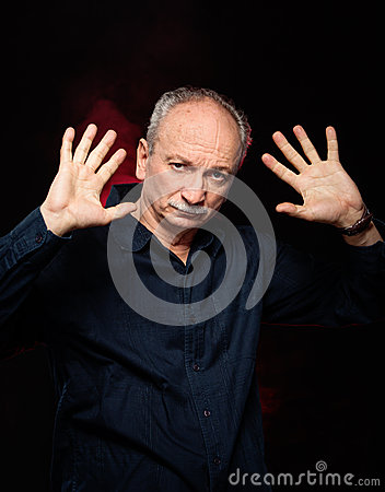 Elderly man with hands up