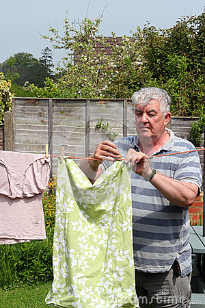 Elderly man hanging out the washing.