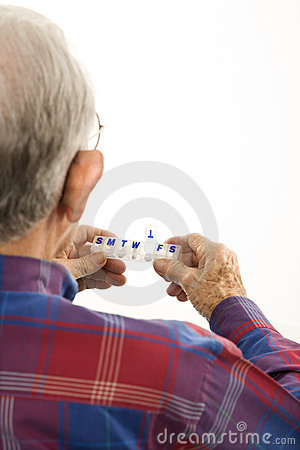 Elderly man holding seven-day pill box.