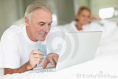 Elderly man lying on bed and shopping online