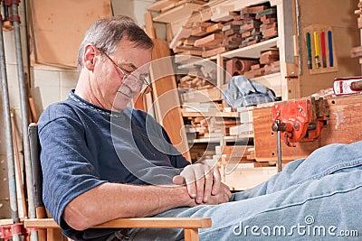 Elderly man peacefully resting in workshop chair