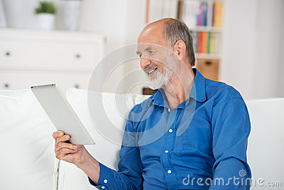 Elderly man reading the screen of his tablet-pc
