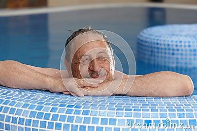 Elderly man relaxing in spa smiling