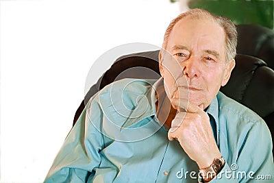 Elderly man sitting in chair , thinking
