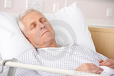 Elderly man sleeping in hospital bed