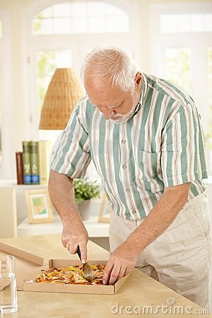Elderly man slicing up pizza.