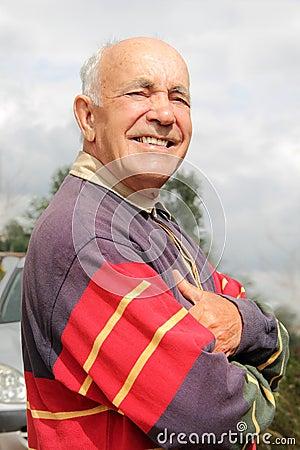 An elderly man smiling in the sun
