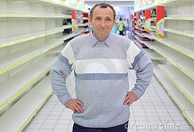 Elderly man stands between empty shelves in  shop