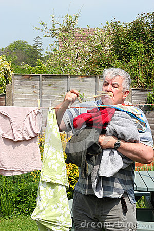Elderly man stressed hanging out the laundry.