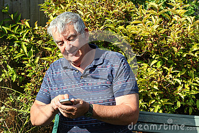 Elderly man texting on his mobile phone.