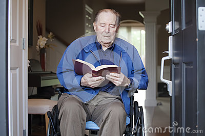 Elderly man in wheelchair reading the Bible
