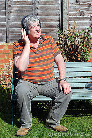 An elderly man with wireless headphones.