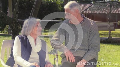 Elderly man and woman speaking in the garden seated on a chair, sunlight coming from the sky stock footage