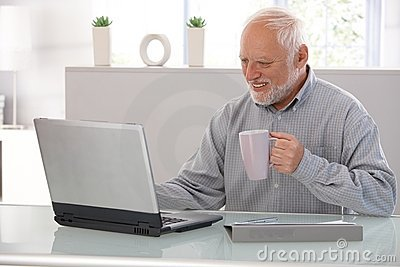 Elderly man working on laptop smiling