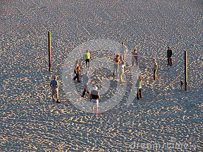 Elderly playing volleyball on isolated beach Editorial Stock Photo