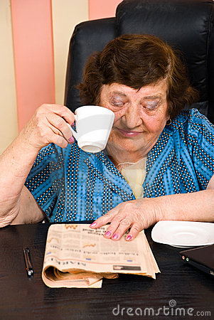 Elderly reading news and drink cup of coffee
