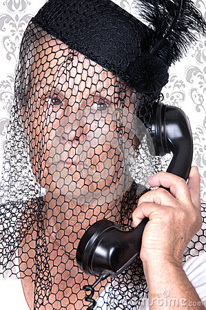 Elderly widow talking on old phone