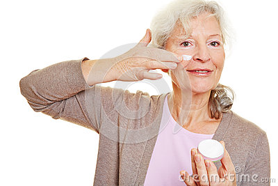 Elderly woman applying lotion