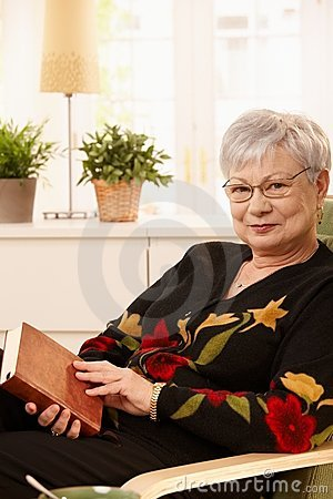 Elderly woman in armchair with book
