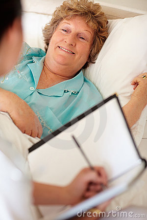 Elderly woman in bed getting a checkup a doctor