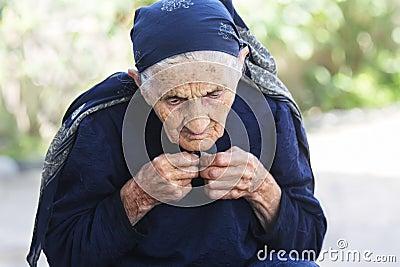 Elderly woman buttoning dress up
