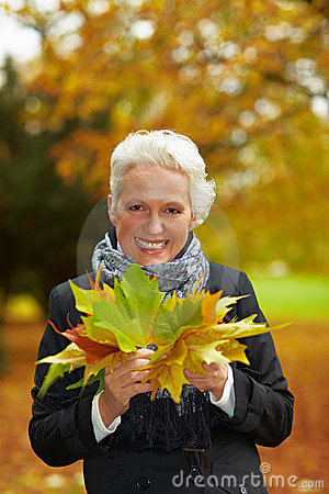 Elderly woman collecting maple