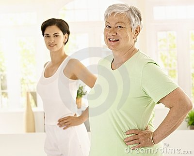 Elderly woman doing exercises with trainer