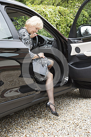 Elderly woman driver and handbag getting out of car