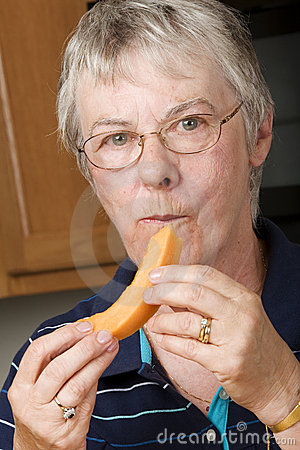 Elderly woman eating fresh cantaloupe