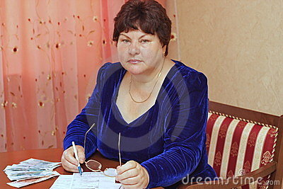 An elderly woman  fills receipts