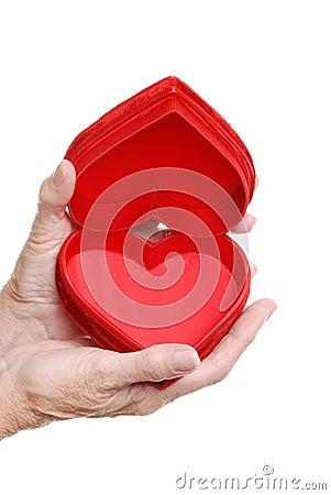 Elderly woman hands holding an open red heart box