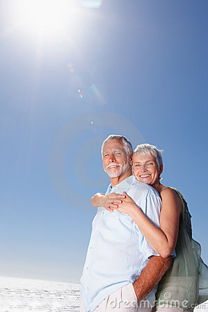 Elderly woman with her arms around her husband