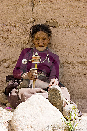 Elderly woman holding prayer wheel Editorial Stock Image