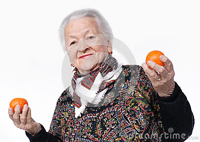 Elderly woman holding two tangerines i