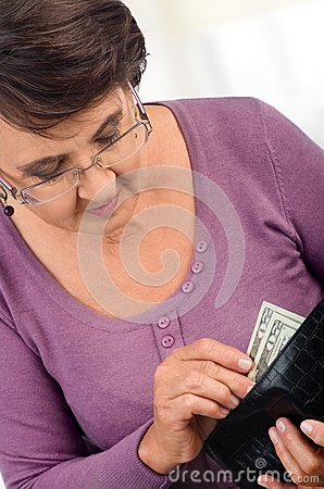 Elderly woman holding wallet with money