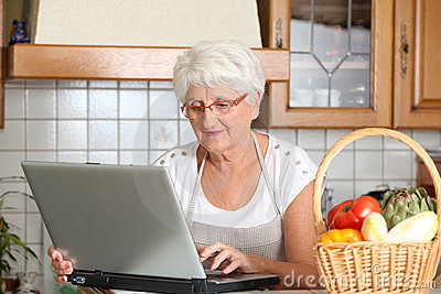 Elderly woman in kitchen looking for recipe