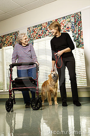 Elderly woman with middle-aged woman walking dog.