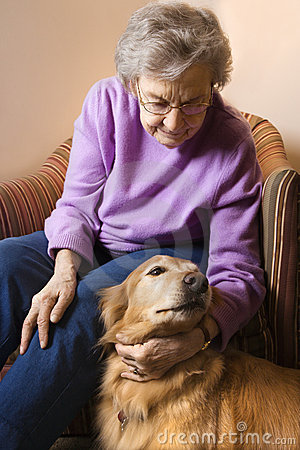 Elderly woman petting dog.