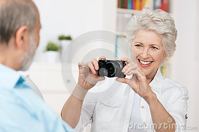 Elderly woman photographing her husband