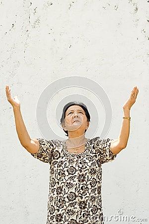 Elderly woman raising hands to worship